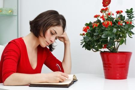 writing book: Ritratto di una bella giovane donna che indossa top rosso, seduto a casa alla sua scrivania, guardando in basso e scrivere, fiori, verde e rosso in vaso rosso Archivio Fotografico