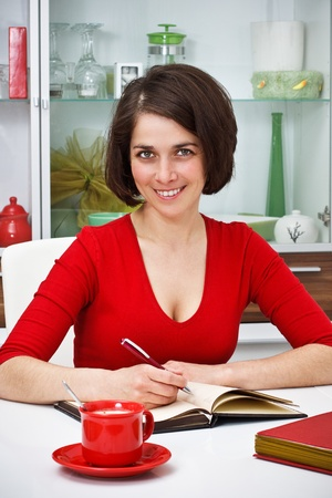 Portrait of a beautiful young woman wearing red top, sitting at home at her desk, writing, smiling into camera, red cup is on desk photo