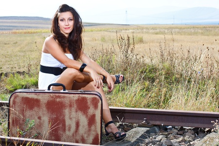An attractive young woman with long brown hair, wearing white mini dress, sitting on suitcase on railroad, smiling into camera photo