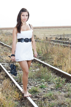 wind blown hair: An attractive young woman with long brown hair blown by the wind, wearing a white mini dress and holding a black high-heel sandal in her right hand is walking bare feet on the railway