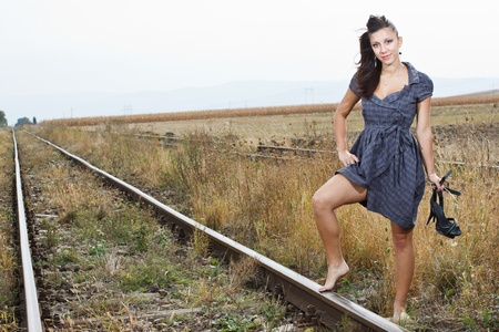 A beautiful young woman with long brown hair, wearing a blue dress, standing with one leg on the rail road and hitch-hiking photo