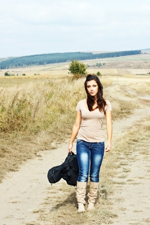 A beautiful young woman with long brown hair blown by the wind, wearing boots, jeans and a top, carrying her guitar in the countryside photo