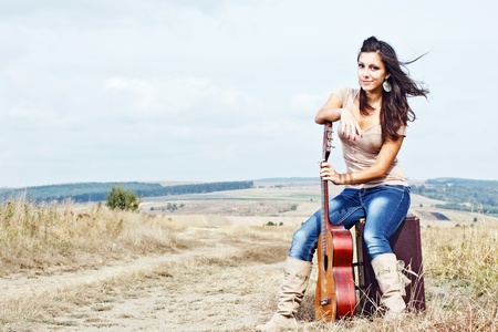 A beautiful young woman with long brown hair blown by the wind, wearing boots, jeans and a top, is sitting on a suitcase, and leaning on her guitar,countryside in the background