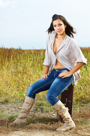 wind blown hair: A beautiful young woman with long brown hair blown by the wind, wearing boots, jeans and a top, is sitting on a suitcase, smiling into camera, countryside in background Stock Photo