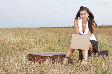 A smiling beautiful young woman with long brown hair,wearing a white top and black mini skirt,is sitting in the medow, holding a blank sheet in her hand, her suitcase is next to her, Stock Photo