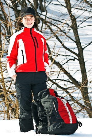 Portrait of a beautiful young woman going on trip with sporty clothes, cap, rucksack, smiling into camera
