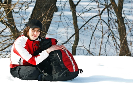 Portrait of a beautiful young woman going on trip with sporty clothes, cap, rucksack, sitting next to her rucksack, smiling into camera Stock Photo