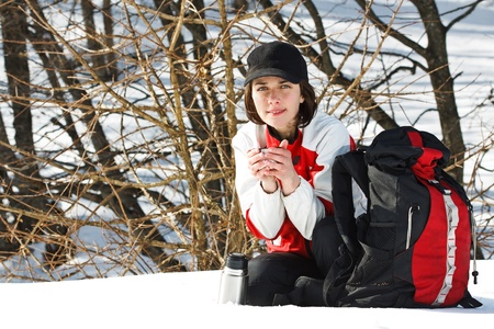 Portrait of a beautiful young woman going on trip with sporty clothes, cap, rucksack, sitting next to her rucksack, smiling, holding a cup of hot drink in her hands Stock Photo