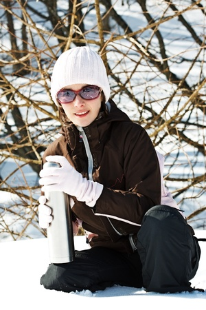 Portrait of a young woman in snowy winter forest, wearing sporty winter clothes, sunglasses, holding a thermos bottle, smiling into camera Stock Photo