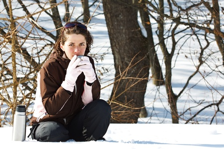 Portrait of a young woman in snowy winter forest, wearing sporty winter clothes, holding the cup of thermos bottle with some hot drink, smiling into camera