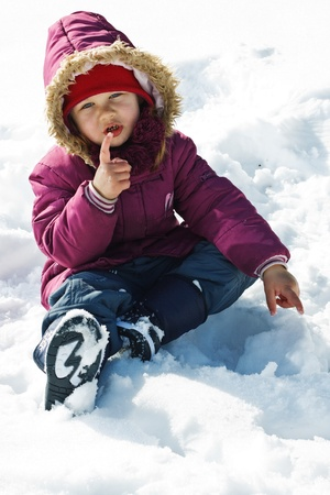 Portrait of a cute 3-year-old girl playing outdoors, sitting in snow in winter clothes, pointing with her finger, looking into camera Stock Photo