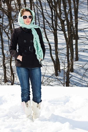 Portrait of a young woman standing in snowy winter forest, wearing scarf on her head, black coat, jeans, white boots, sunglasses