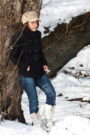 Portrait of a young woman standing in snowy winter forest, wearing a cap, black coat, jeans, white boots, standing by a tree, looking away