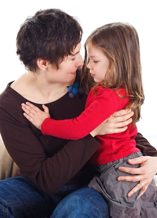 rtrait of a cute 3-year-old girl and her young mother hugging each other - isolated on white