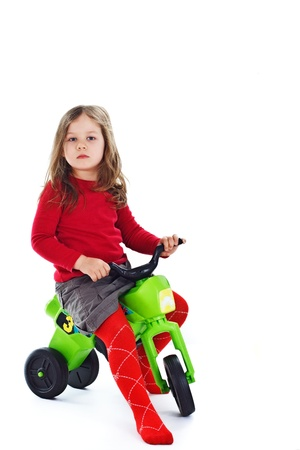 Portrait of a beautiful 3-year-old girl, wearing red top, red tights and grey skirt, playing with tricycle - isolated on white