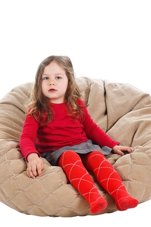 Portrait of a beautiful 3-year-old girl, wearing red top, red tights and grey skirt, sitting on soft stool, looking into camera - isolated on white Stock Photo