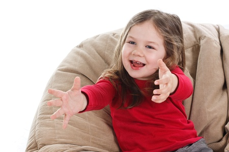 Portrait of a beautiful 3-year-old girl playing, wearing red top, stretching her arms out, waiting for a ball, laughing - isolated on white