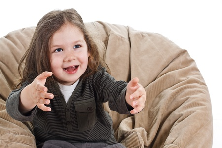 Portrait of a beautiful 3-year-old girl playing, stretching her arms out, waiting for a ball, laughing - isolated on white Stock Photo
