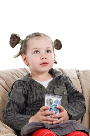Portrait of a beautiful 3-year-old girl with pigtails, holding a cup in her hands, looking up with an amazed expression - isolated on white Stock Photo
