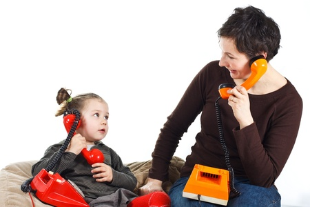 Portrait of a cute 3-year-old girl and her young mother playing, phoning with retro telephones, one red, one orange, looking at each other - isolated on white photo