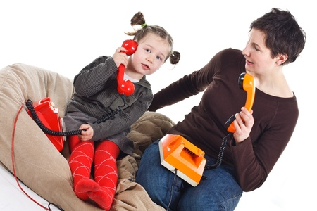 Portrait of a cute 3-year-old girl and her young mother playing, phoning with retro telephones, one red, one orange - isolated on white Stock Photo