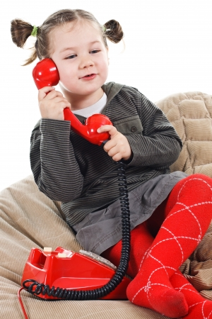 Portrait of a beautiful 3-year-old girl, wearing green top, red tights and grey skirt, playing with a red retro telephone, speaking into the receiver, smiling - isolated on white