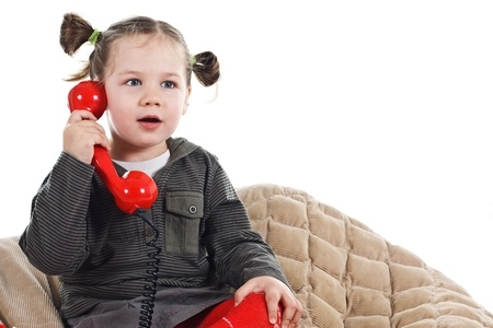 Portrait of a beautiful 3-year-old girl, wearing green top, red tights and grey skirt, playing with a red retro telephone, speaking into the receiver, looking surprised - isolated on white photo