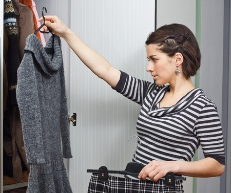 Portrait of a beautiful young woman standing at her wardrobe trying to choose a piece of clothes