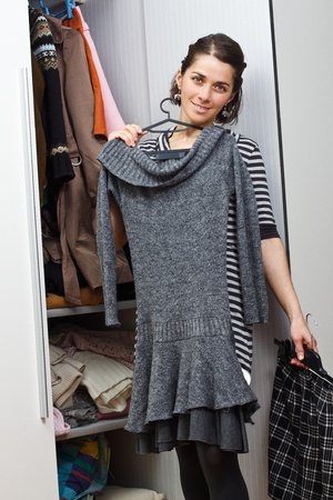 Portrait of a beautiful young woman standing at her wardrobe trying to choose a piece of clothes, smiling into camera photo