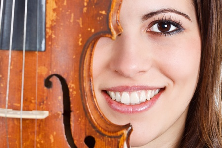 Close-up of a beautiful young womans face half behind a violin