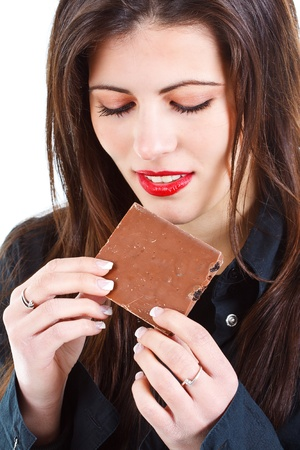 Portrait of a beautiful young woman with long brown hair, eating a bar of chocolate, looking down on it - isolated on white