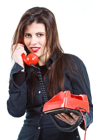 Portrait of a beautiful young woman with long brown hair, holding a red retro telephone, smiling - isolated on white