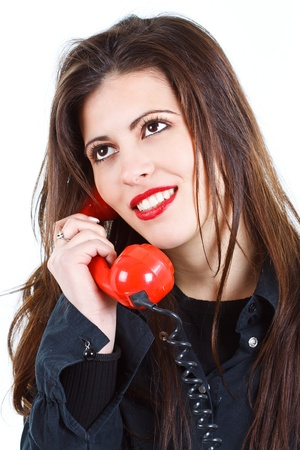 Portrait of a beautiful young woman with long brown hair, holding a red retro telephone receiver, smiling, looking up - isolated on white Stock Photo