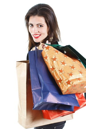 Portrait of a beautiful young woman with long brown hair with colourful shopping bags on her back, smiling back into camera - isolated on white