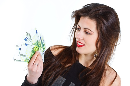 Portrait of a beautiful young woman with long brown hair, looking at banknotes that she is holding in her hands - isolated on white photo