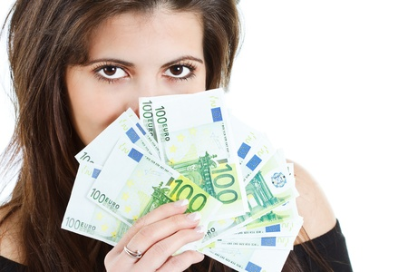 Close-up of banknotes - euros - held by a beautiful young woman with long brown hair, hiding behind the money, big brown eyes seen - isolated on white