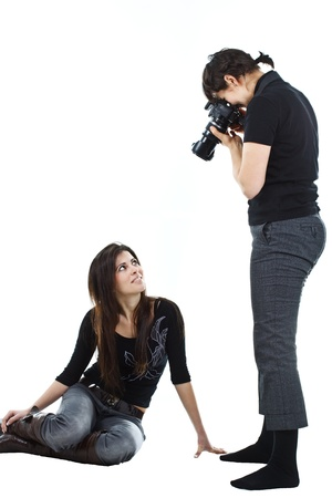 Portrait of a model posing while a woman photographer is taking photos of her in a studio - isolated on white
