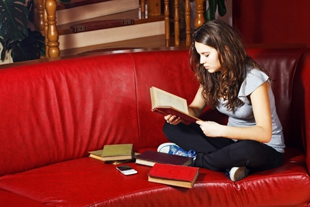 Portrait of a beautiful teenage girl with long brown hair, sitting with crossed legs on the sofa at home, reading a book, surrounded by books Stock Photo