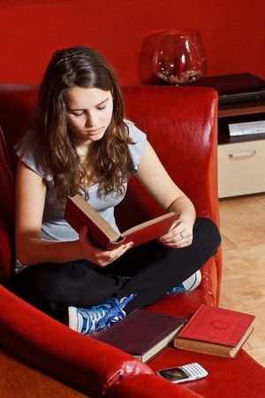 Portrait of a beautiful teenage girl with long brown hair, sitting with crossed legs on the sofa at home, reading a book, more books in front of her