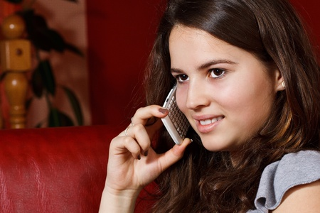 Portrait of a beautiful teenage girl with long brown hair, using her mobile phone, smiling - indoors, at home Stock Photo