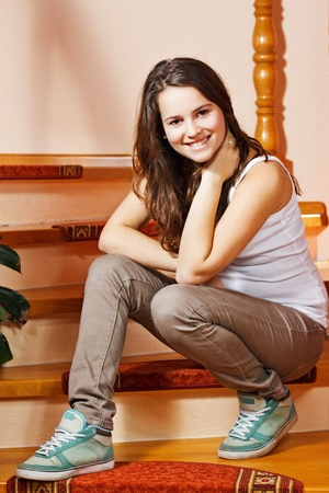 Portrait of a beautiful teenage girl with long brown hair, sitting on stairs at home, smiling into camera Stock Photo
