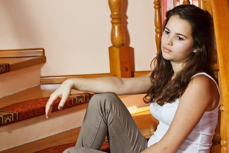 Portrait of a beautiful teenage girl with long brown hair, sitting on stairs at home looking depressed Stock Photo