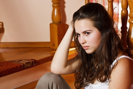 depressed women: Portrait of a beautiful teenage girl with long brown hair, sitting on stairs at home looking depressed Stock Photo