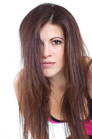 Portrait of a young beautiful woman with long brown hair, one eye is covered by her hair - isolated on white