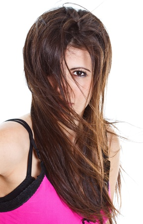 Portrait of a young beautiful woman with long brown hair, one eye is covered by her hair blown by wind - isolated on white