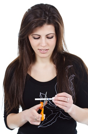 Portrait of a beautiful young woman with long brown hair cutting a cigarette into two with a pair of scissors, looking down at cigarette - isolated on white Stock Photo