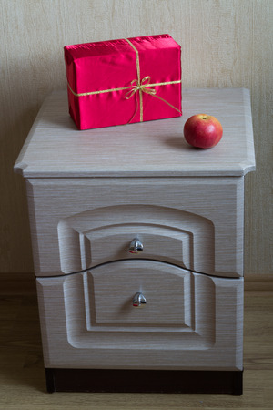 nightstand: Red Gift and apple on the nightstand.