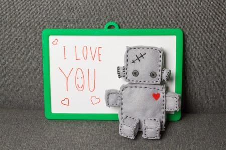 carta de amor: Robot Con la tarjeta del texto. Juguete suave macro en backgroung textil. Foto de archivo
