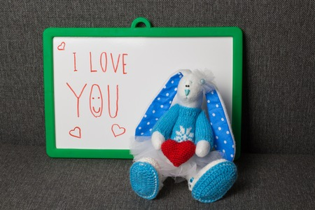i love you sign: Bunny With Text Board. Macro Soft Toy at blurred backgroung. Stock Photo