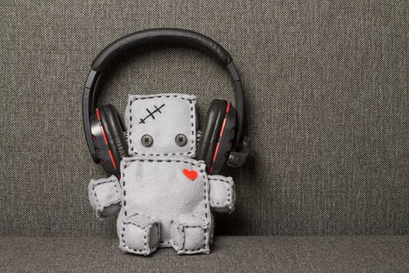 soft textile: Robot With Headset. Macro Soft Toy at textile backgroung.